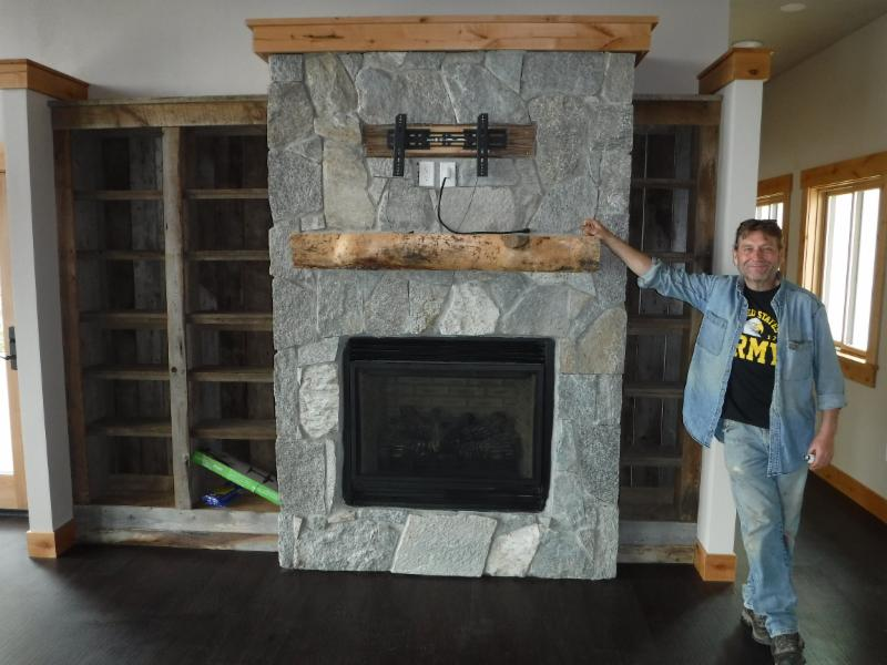 The mason shows off the fireplace surround with split-log mantel.