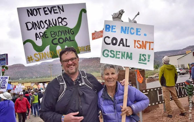 A man and woman holding signs at a mining rally
