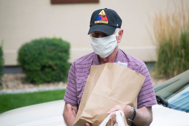 GREELEY, CO, July 30: Terry Cross carries groceries he picked up for a senior client of 60+ Rides to the client's door. Cuyler Meade/Staff reporter