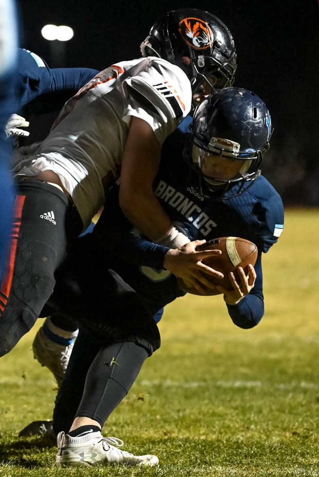 KERSEY, CO - OCTOBER 23:Sterling's Brady Albrandt (57) tries to stop Platte Valley's Kade McDaniel (16) on a keeper but canÕt prevent the touchdown during the Platte Valley Broncos football game against the Sterling Tigers at Platte Valley High School in Kersey Oct. 23, 2020. The Broncos fell to the Tigers 31-21. (Alex McIntyre/Staff Photographer)