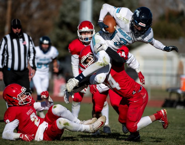 EATON, CO - NOVEMBER 14:Platte Valley's Devyn Lauer (13) leaps over Eaton's Walker Martin (2) and Eaton's Salvador Rojas (14) to bring the Broncos to first-and-goal during the Eaton Reds football regular season finale against the Platte Valley Broncos at Eaton High School in Eaton Nov. 14, 2020. The Platte Valley Broncos defeated the Eaton Reds 41-35. (Alex McIntyre/Staff Photographer)