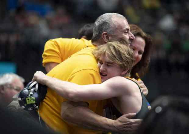 Windsor s Vance VomBaur hugs Rick Perez, his friend and teammate Tristian Perez s father, after defeating Longmont s John Nicholas in the 138-pound final to win the state title during the CHSAA High School State Wrestling Championships in the Pepsi Center in Denver on Saturday, Feb. 22, 2020. (Greeley Tribune file photo)