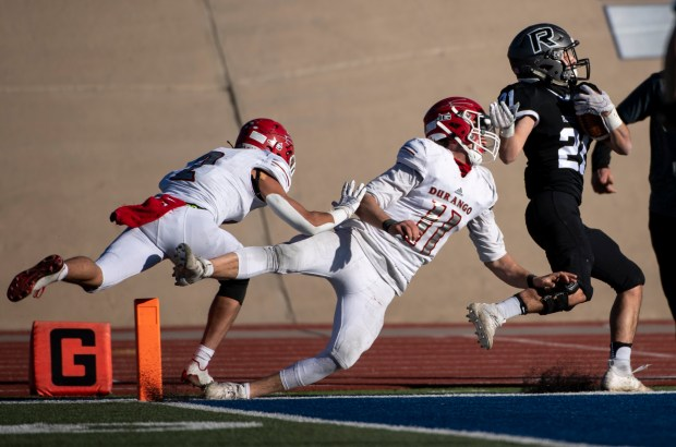 PUEBLO, CO - DECEMBER 05:Roosevelt's Keegan Sterkel (21) shakes off Durango's Jordan Woolverton (11) and Durango's Gage Mestas (2) as he runs into the end zone to score a touchdown during the Roosevelt Rough Riders game against the Durango Demons in the CHSAA Class 3A football state championship at the Neta and Eddie DeRose ThunderBowl at Colorado State University-Pueblo in Pueblo Dec. 5, 2020. The Roosevelt Rough Riders fell to the Durango Demons 21-14. (Alex McIntyre/Staff Photographer)