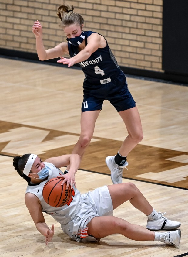GREELEY, CO - JANUARY 27:University's Kylie Kravig (4) leaps over Greeley Central's Tathis Arredondo (22) as Arredondo slips and falls during the second half of the Greeley Central Wildcats girls basketball game against the University Bulldogs at Greeley Central High School in Greeley Jan. 27, 2021. The Bulldogs defeated the Wildcats 54-42. (Alex McIntyre/Staff Photographer)
