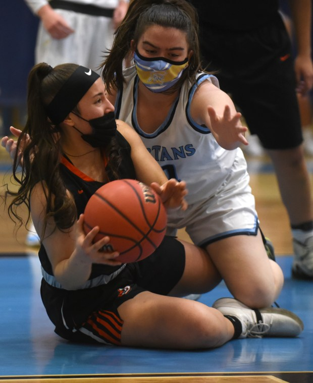 Greeley Central's Tathis Arredondo tries to find an open teammate as she struggles to keep the ball away from Greeley West's Lauren Wagley during the game Monday night at Greeley West High School. (For the Greeley Tribune/Joshua Polson)