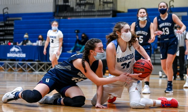 KERSEY, CO - FEBRUARY 13:University's Miranda Wiedeman (45) tries to wrestle the ball from Platte Valley's Bree Bunting (31) on the floor during the Platte Valley Broncos girls basketball game against the University Bulldogs at Platte Valley High School in Kersey Feb. 13, 2021. The Broncos defeated the Bulldogs 40-36. (Alex McIntyre/Staff Photographer)