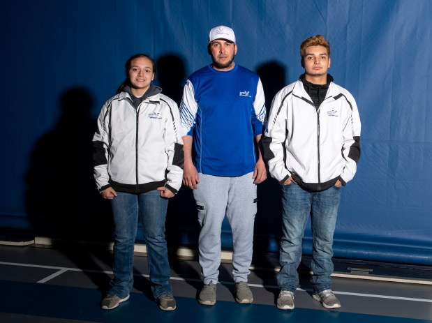 KERSEY, CO - MARCH 30:Platte Valley Broncos wrestler Neveah Garcia, left, stands for a portrait alongside her coach, Devin Wolf, center, and brother, Jeremiah Garcia, right, outside the wrestling room in Platte Valley Middle School in Kersey March 30, 2021. Neveah Garcia took home the state title for the 161-pound weight class in girls wrestling's first official season as a CHSAA-sanctioned sport. (Alex McIntyre/Staff Photographer)
