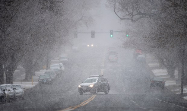 GREELEY, CO - MARCH 13:A car pulls out onto 11th Avenue from a side street just north of 20th Street as snow falls in Greeley March 13, 2021. The storm is forecasted to bring as much as 18 inches of snow to the Greeley area over the weekend. (Alex McIntyre/Staff Photographer)