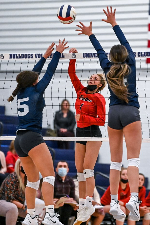 GREELEY, CO - APRIL 06:Eaton's Ahana Leffler (1) attacks as University's Kylie Williams (5) and University's Aesha Alrashed (4) leap to block during the University Bulldogs volleyball game against the Eaton Reds at University Middle School in Greeley April 6, 2021. The Reds defeated the Bulldogs 3-1. (Alex McIntyre/Staff Photographer)