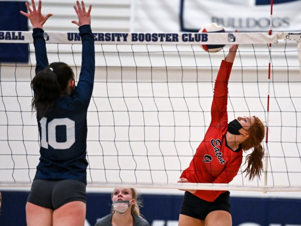 GREELEY, CO - APRIL 06:Eaton's Abbey Hays (9) attacks as University's Chloe Ruhl (10) leaps to block during the University Bulldogs volleyball game against the Eaton Reds at University Middle School in Greeley April 6, 2021. The Reds defeated the Bulldogs 3-1. (Alex McIntyre/Staff Photographer)