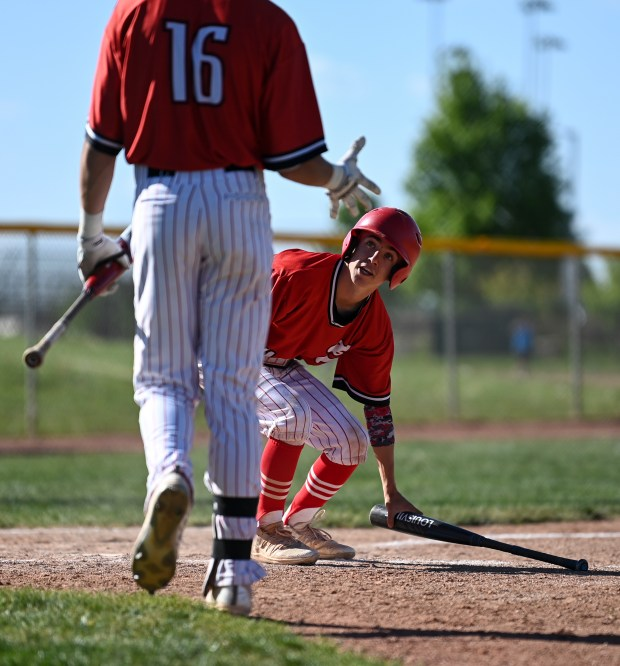 GREELEY, CO - MAY 27:Eaton's Walker Martin (16) congratulates Eaton's Ben Richter (4) as Richter picks up a bat at home plate after being batted in during the Eaton Reds baseball gamer against the University Bulldogs at University High School in Greeley May 27, 2021. The Reds defeated the Bulldogs 12-5. (Alex McIntyre/Staff Photographer)