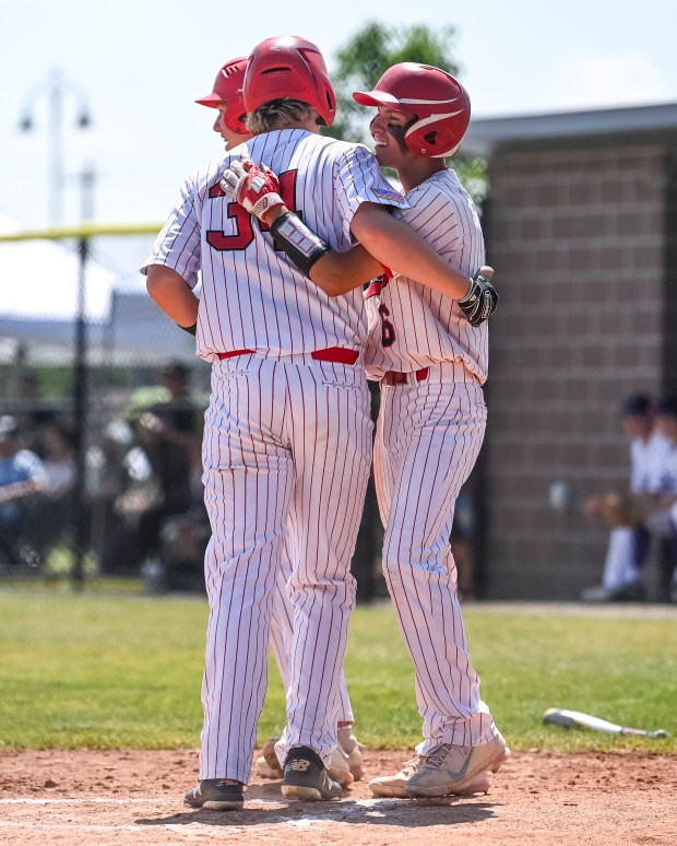 FREDERICK, CO - JUNE 25:Eaton's Jared McCormack (33) embraces Eaton's Hayden Vigueria (6) and Eaton's Tate Smith (34) after Vigueria and Smith scored to give the Reds a 2-1 lead during the Eaton Reds state semifinal baseball game against the Lutheran Lions at Frederick High School in Frederick June 25, 2021. The Eaton Reds defeated the Lutheran Lions 2-1. (Alex McIntyre/Staff Photographer)