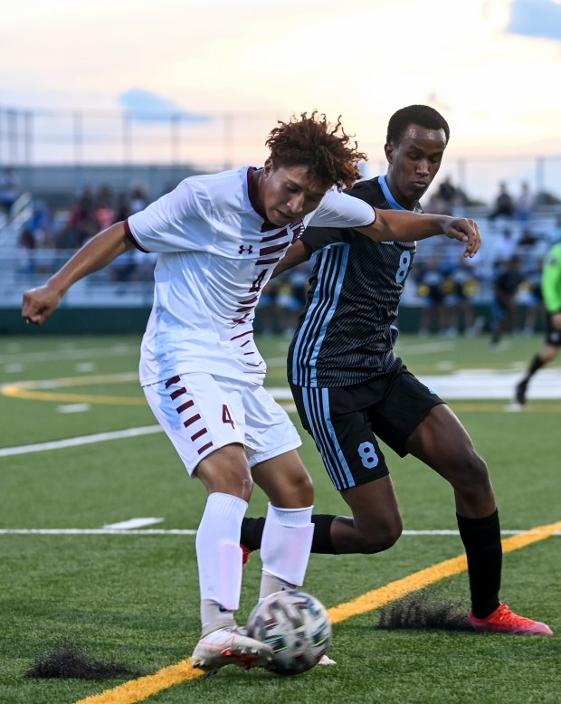 GREELEY, CO - AUGUST 26:Northridge's Roberto Manza (4) kicks as Greeley West's Abdi Abdifatah (8) closes in during the Greeley West Spartans boys soccer match against the Northridge Grizzlies at District 6 Soccer Stadium in Greeley Aug. 26, 2021. The Grizzlies and Spartans played to a 1-1 draw through two overtime periods. (Alex McIntyre/Staff Photographer)