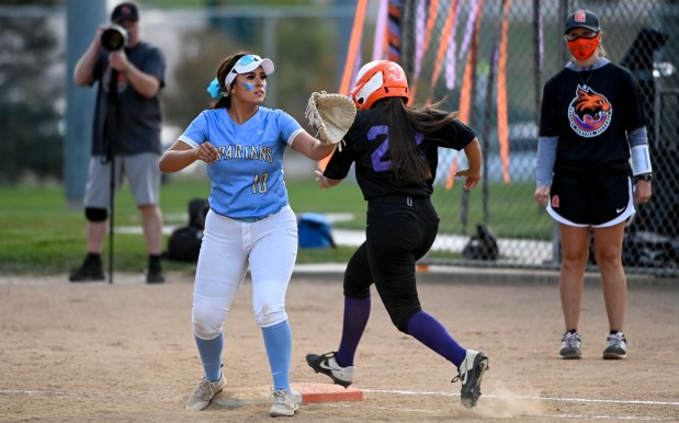 GREELEY, CO - SEPTEMBER 23:Greeley Central's Tathis Arredondo (22) runs safely to first as Greeley West's Brookelynn Hernandez (10) isn't thrown the ball in time to tag her out during the Greeley Central Wildcats softball game against the Greeley West Spartans at Greeley-Evans Youth League Complex in Greeley Sept. 23, 2021. The Wildcats dedicated the game to the Best Buddies club with special purple-accented uniforms, and club member Xavier Reichel threw the honorary first pitch. (Alex McIntyre/Staff Photographer)