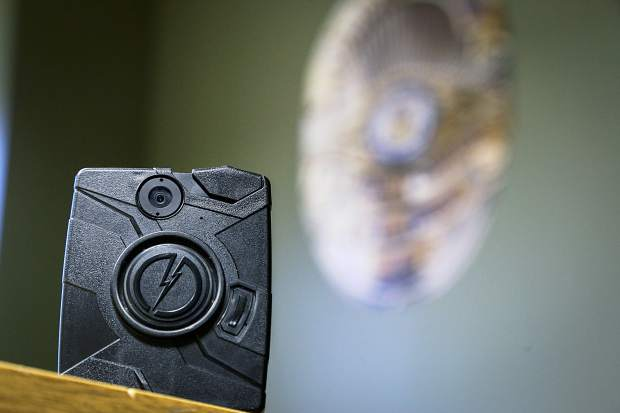 A police officer's body camera is placed on a table inside the Evans Community Building, which houses the Evans Police Department. The body cameras are worn on an officer's chest, and they are roughly the size of a deck of cards.