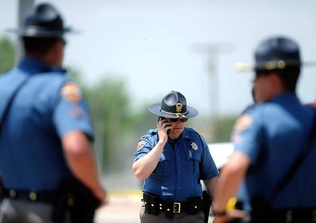 A Colorado State trooper talks on the phone at the scene of a crash after Greeley Police, Weld County Sheriffs, and several other law enforcement agencies were led on a high speed chase down U.S 85.
