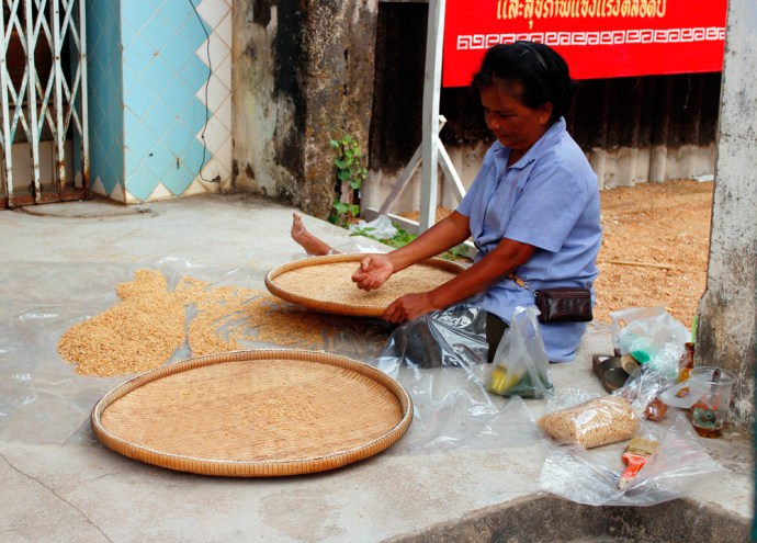 A lady sorts out the rice in Takuapa market