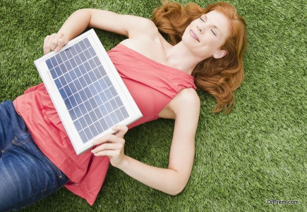 Beautiful woman lying on grass while holding solar panel