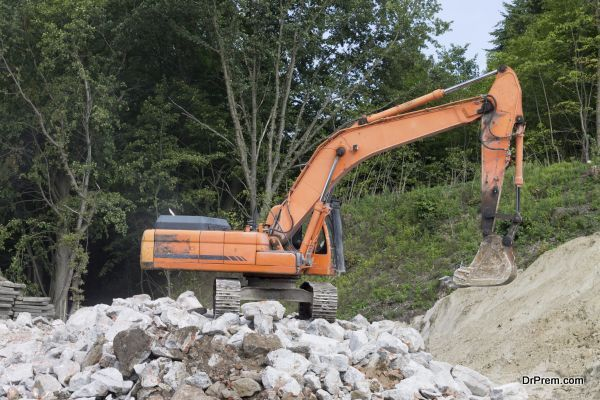 Working excavator during the removal of stones from the destroye