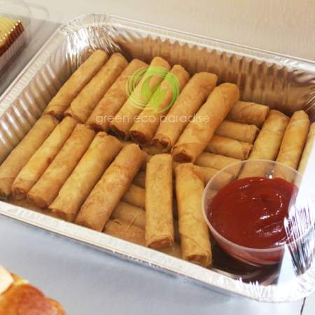Fried spring rolls with dipping sauce in a catering tray.