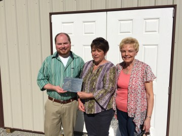 Son Ministries food storage building plaque presentation - L-R: Brandon Sparks, Foundation Program Manager; Cindy Hale of Son Ministries; Linda Haseman, Foundation board and committee member