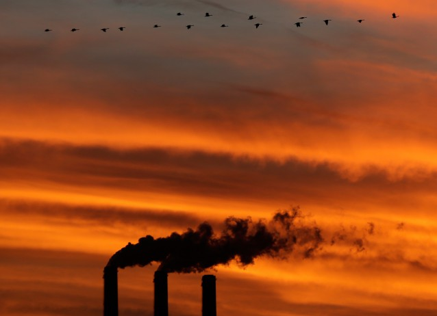 A flock of Geese fly past the smokestacks at the Jeffrey Energy Center coal power plant as the sun sets near Emmett, Kansas.
