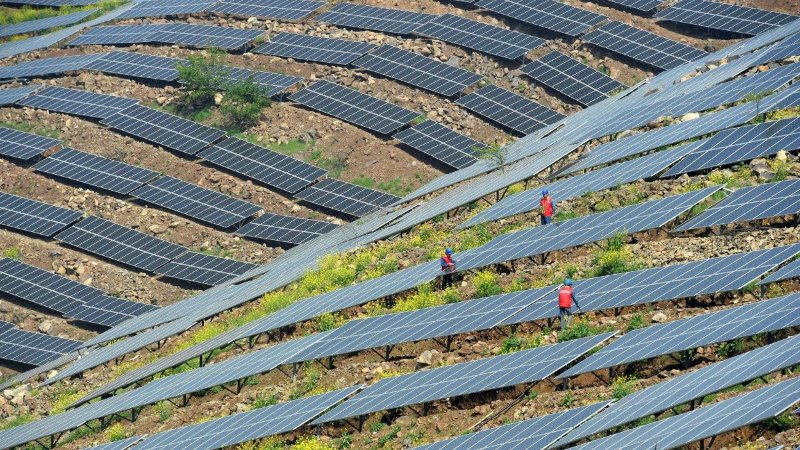 Chinese workers checking PV modules (© AFP)