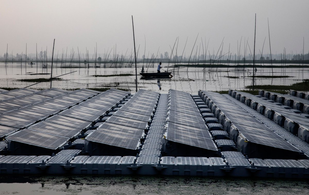 Fisherman and solar panels (Kevin Frayer | Getty Images)