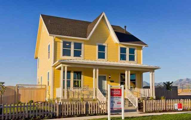 Yellow house with for sale sign