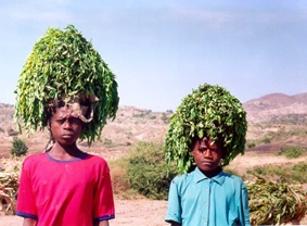 Two woman wearing moringa leaves