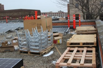 Modules, mounting racks and ballast blocks are hoisted by crane to the rooftop