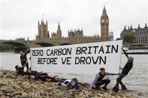 "Environmental activists hold a banner which reads ""Zero carbon Britain before we drown"" on the banks of the Thames outside of the Houses of Parliament in London"