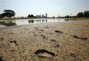 Footprints mark the bank of a partially dried-up pond near downtown Dallas