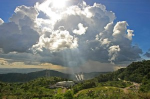 Sun shining through the clouds on a geothermal power plant