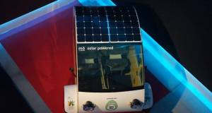 The evovelo hybrid tricycle is being shown off with solar panels on its roof.