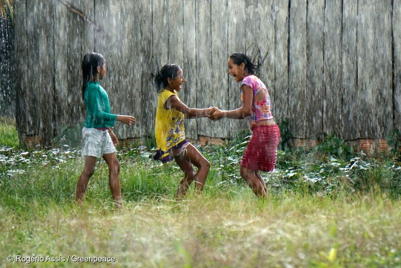 Munduruku children playing in the rain in Sawré Muybu village. Sawré Muybu village serves as headquarters for the action on March 18th, 2016. A 20x30 meters banner is to be opened near the Tapajós river, protesting against the construction of dams in the region. Warriors from other villages and Greenpeace activists gather in the village. A aldeia Sawré Muybu recebe os preparativos para a ação do dia 18/03/2016, em que um banner de 20x30 metros deve ser aberto próximo ao Rio Tapajós, em protesto à construção de hidrelétricas na região. Guerreiros de outras aldeias e ativistas do Greenpeace chegam à aldeia. 15/03/2016. Foto: Rogério Assis/Greenpeace.