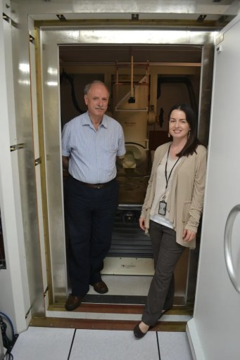 Dr. Apostolos Georgopoulos and research technician Maggie Mahan at door of magnetically shielded scanning vault
