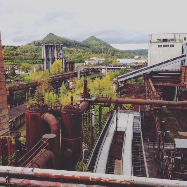 Kontraste: Rohre, Schienen, Kessel und Transportschächte im Weltkulturerbe Völklinger Hütte und dahinter grüne Hügel und Wälder.
