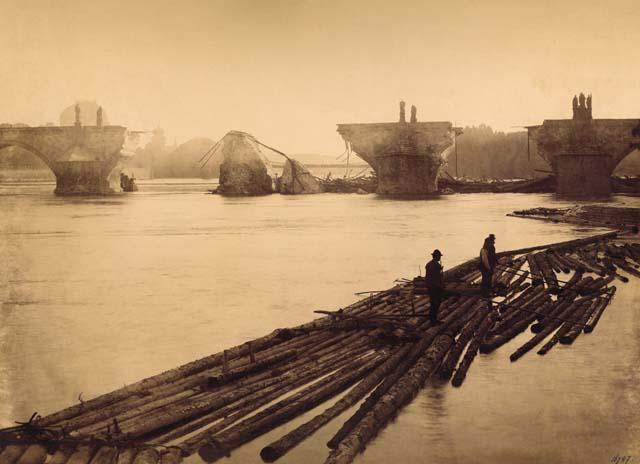 Bei der Flößerei wird die Wasserenergie zum Transport von Holz genutzt. 1890: Eine Flut zerstörte mehrere Bögen der Karlsbrücke in Prag.  Vorne: Flößer transportieren Baumstämme über das Wasser  (commons.wikimedia.org, Fotograf unbekannt).