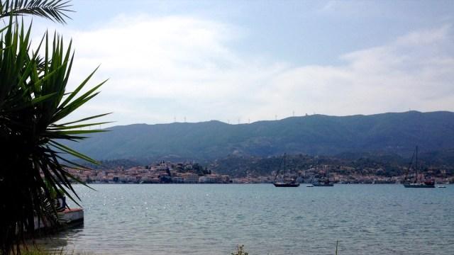 Abendspaziergang: Der Fußweg von der Villa Irene in die Stadt von Poros führt an meiner Hausbucht entlang, vorbei an Stegen mit Fischerbooten und Anlegern für Segelboote und Yachten (Poros, Griechenland, September 2020).