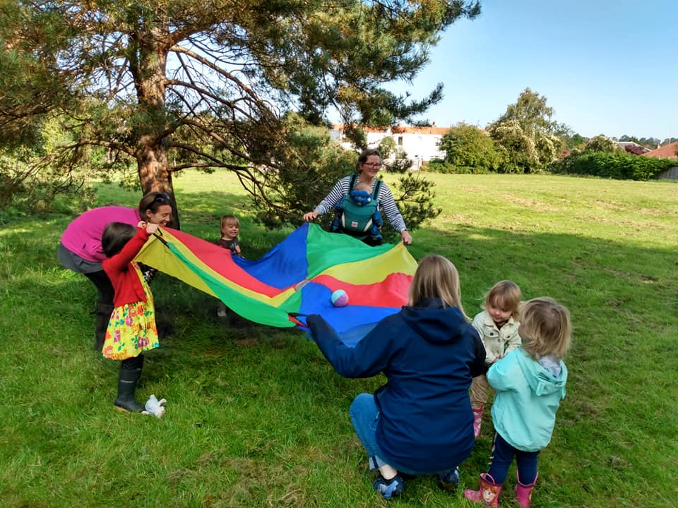 young children and parents playing games with a colourful parachute