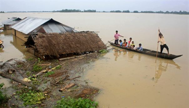 Flood-affected local residents move to safer places on a boat next to their damaged huts after heavy rains at Jajimukh village in the northeastern Indian state of Assam June 27, 2012. Incessant heavy rains in northeast India have caused massive flooding and landslides, killing at least 10 people, local media reported on Wednesday. REUTERS/Stringer (INDIA - Tags: ENVIRONMENT DISASTER)