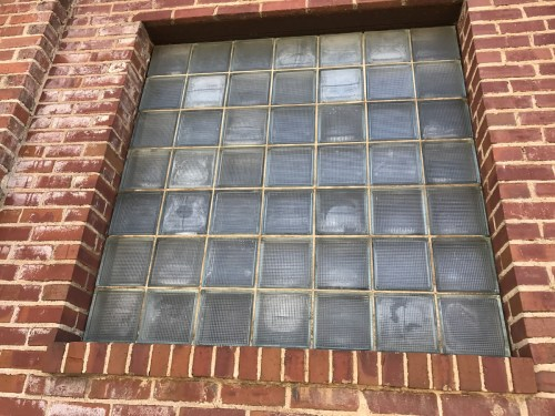 The northern most window bay in the original portion of Grey Hosiery has been partially enclosed around a seven-by-seven glass block window.