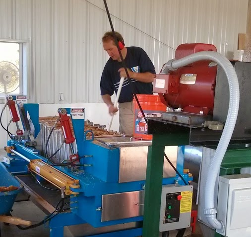 Pete Mitchell of Headwater Cider in Hawley, Mass. operates a modern press, which is a series of mesh baskets squeezed through the force of pneumatic piston.