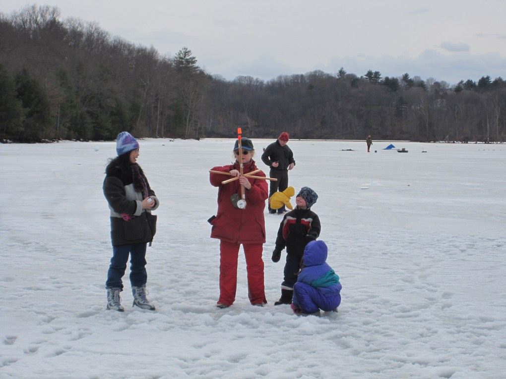 Ice fishing clinic participants examining their tip-up at Barton's Cove, Gill, Mass. in 2010; photo courtesy the Massachusetts Division of Fisheries and Wildlife.