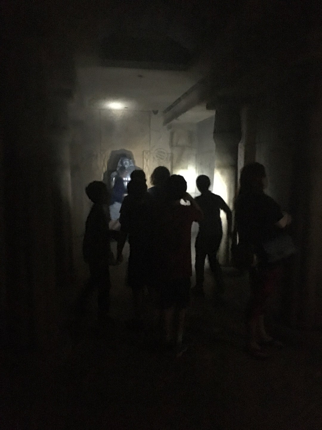 Photo of players entering game space: With only flashlights to see by, the young adventurers make their way into the dreary depths of The Tomb; photo by Regina Velazquez.