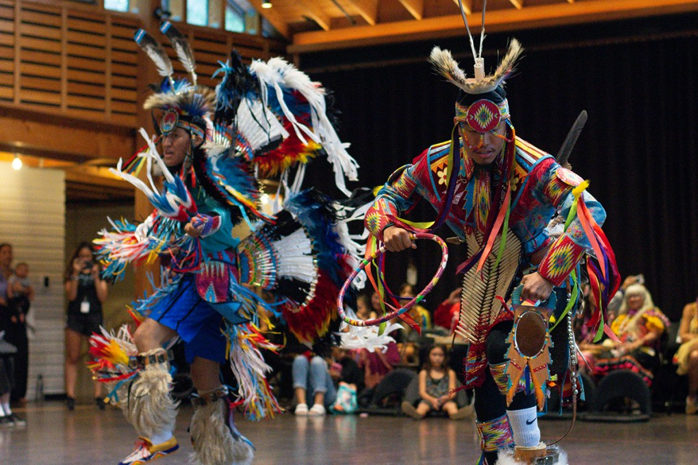 Two indigenous male dancers in elaborate, colorful costumes. The Land On Which We Dance Inside/Out Performance; photo by Grace Kathryn Landefeld.