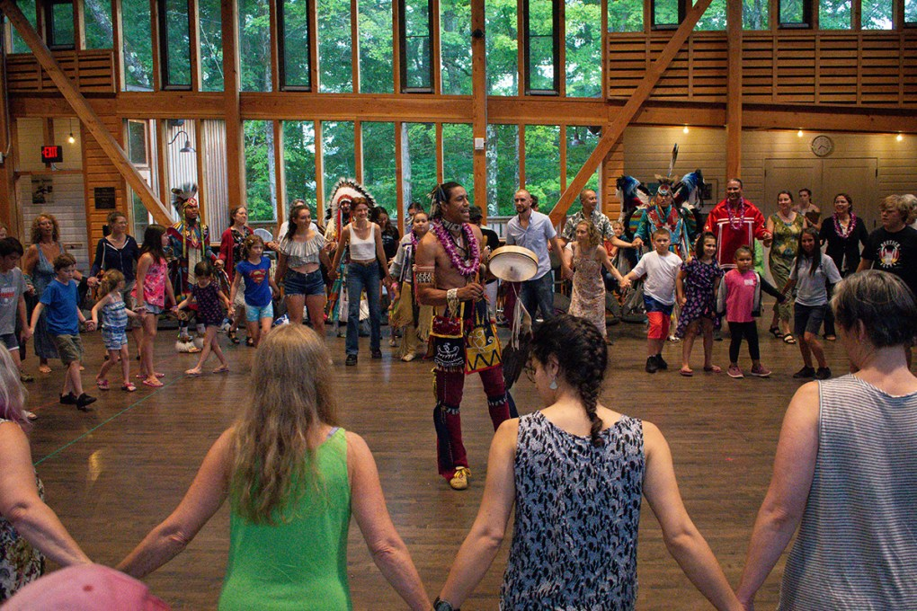 Photo of a large open room filled with people forming a circle and holding hands. Indigenous dancers are at the center of the circle; The Land On Which We Dance Inside/Out Performance; photo by Grace Kathryn Landefeld.