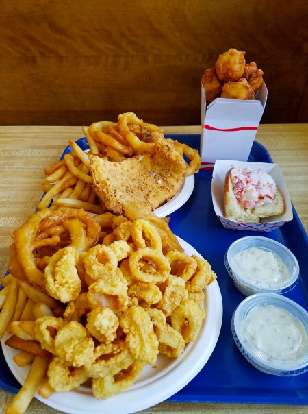Photo of big plates of battered, fried seafood, onion rings, and French fries on a tray, with sides of tartar sauce and a small lobster roll: Woodman's of Essex, while technically just outside of Gloucester in Essex, is a cult favorite for its super-fresh fried fish entrees, served on a heaping pile of French fries and onion rings.; photo by Robin Catalano.