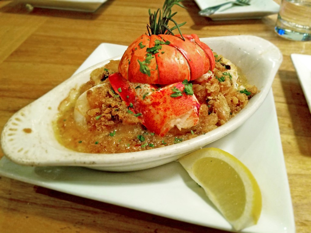 Photo of an oval-shaped shallow bowl (boat) containing seafood casserole, fish, lobster tail, shellfish, sitting on a rectangular plate, with lemon wedge: The buttery, indulgent seafood casserole at Passports on Main Street; photo by Robin Catalano.